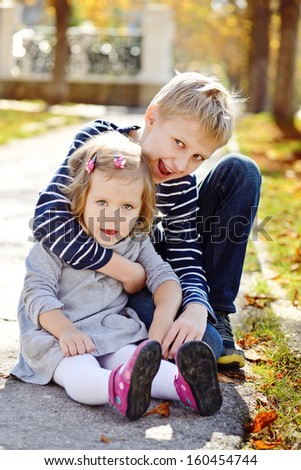 brother and sister outside in fall time - stock photo