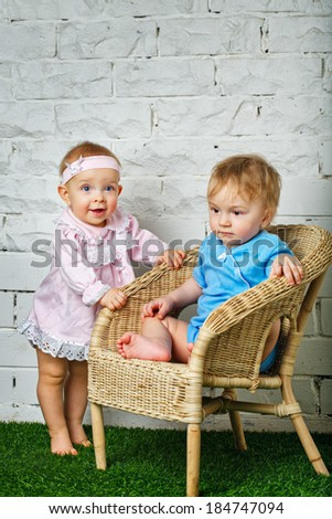 Brother and sister playing in the backyard next to the wicker chair - stock photo