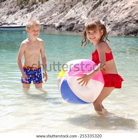 Brother and sister playing in the sea with a ball