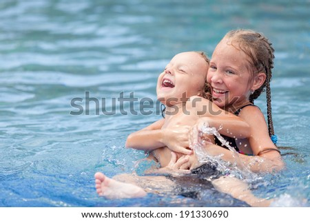brother and sister playing in the swimming pool
