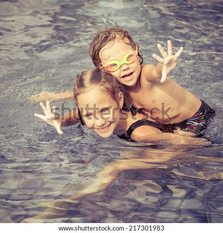 brother and sister playing in the swimming pool at the day time