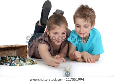 brother and sister playing marbles together - stock photo