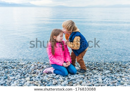 Brother and sister playing on a beach on a nice day in early spring  - stock photo