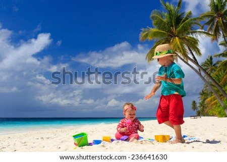 brother and sister playing on tropical sand beach - stock photo