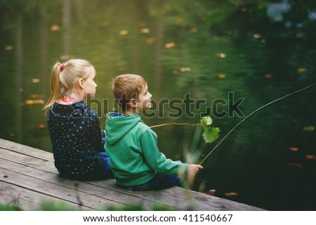 Brother and sister playing outside - imitate fishing at a lake