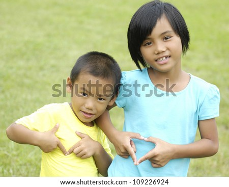 Brother and sister playing outside makes a gesture in the form of the heart - stock photo