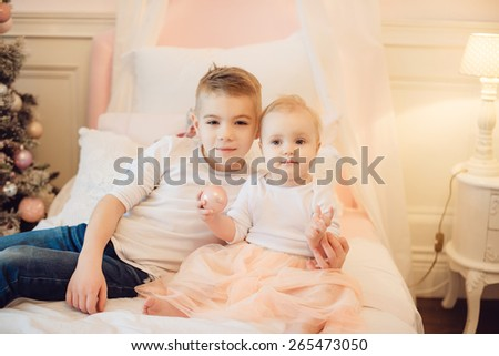 brother and sister playing sitting on a bed, cuddling