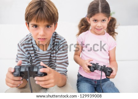 Brother and sister playing video games together on the sofa - stock photo