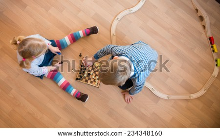Brother and sister playing with chess. Photo from above - stock photo