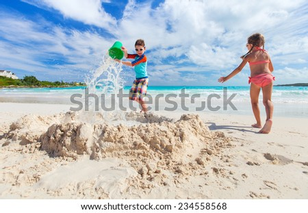 Brother and sister playing with sand at tropical beach - stock photo