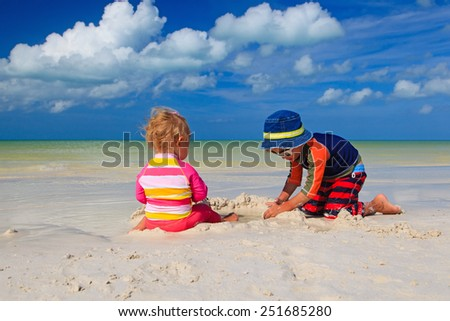 brother and sister playing with sand on tropical beach - stock photo