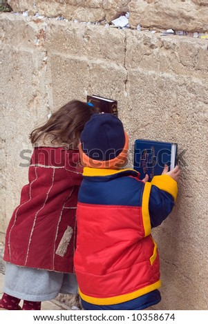 Brother and sister pray in the wailing wall in Jerusalem.