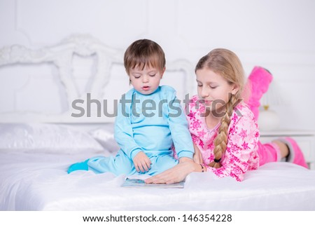 Brother and sister reading a book in bed - stock photo