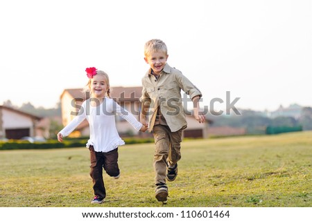 Brother and sister running together outdoors having fun, smiling and laughing - stock photo