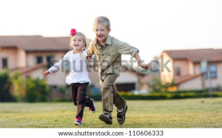 Brother and sister running together outdoors having fun, smiling and laughing