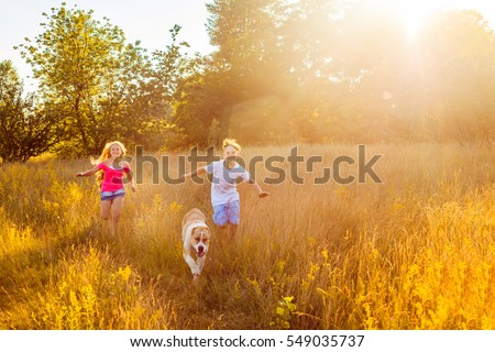 Brother and sister runs in a green field with their beautiful Alabai pet dog.