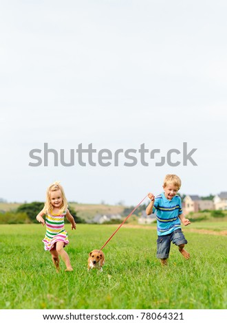Brother and sister runs in a green field with their new pet - stock photo