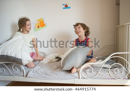 Brother And Sister Sit On The Bed In The Bedroom. They Fight Pillows. Boy