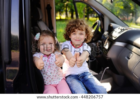 brother and sister sitting in the car. Children sit in the car and smiling