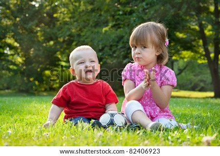 brother and sister sitting on the grass