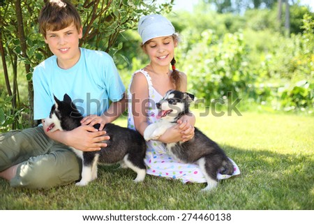 Brother and sister sitting on the grass with two puppies husky - stock photo