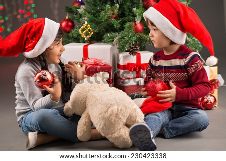 Brother and sister sitting under the Christmas tree and playing with baubles - stock photo