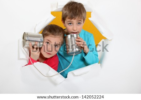Brother and sister speaking into tin can - stock photo