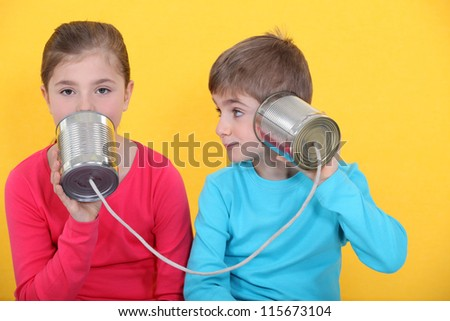 Brother and sister speaking through tin can and string - stock photo