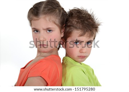 Brother and sister sulking at each other. - stock photo