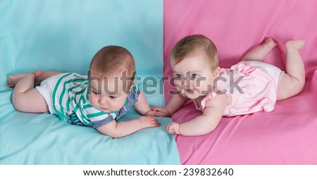 brother and sister - twins babies girl and boy on pink and blue background - stock photo