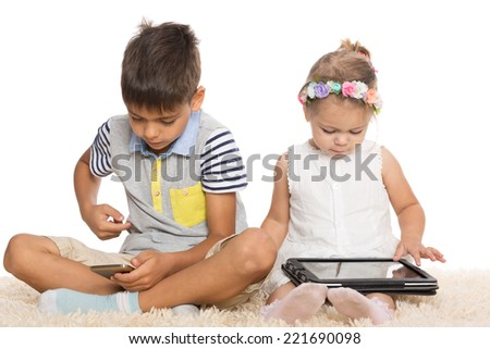 Brother and sister use the tablet PC and smartphone for their games. Six and two years.