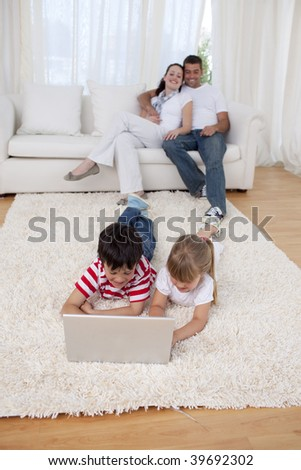 Brother and sister using a laptop on floor in living-room with their parents on sofa - stock photo
