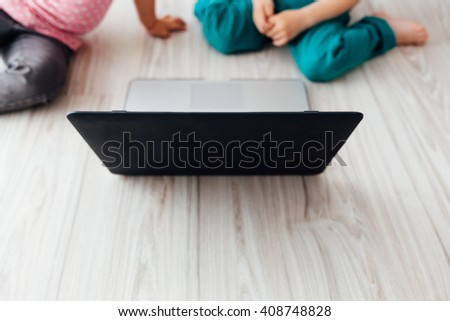 Brother and sister using laptop together. Closeup on laptop. - stock photo