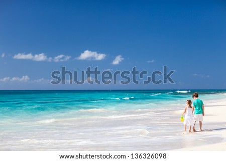 Brother and sister walking along a beach at Caribbean - stock photo