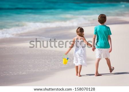 Brother and sister walking along a beach at Caribbean - stock photo