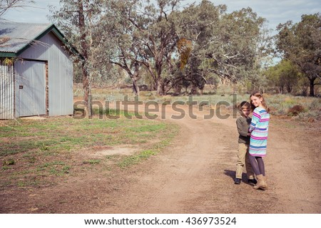 Brother and sister walking down a dirt track in outback Australia - stock photo