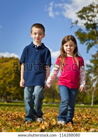 Brother and sister walking holding hands - stock photo