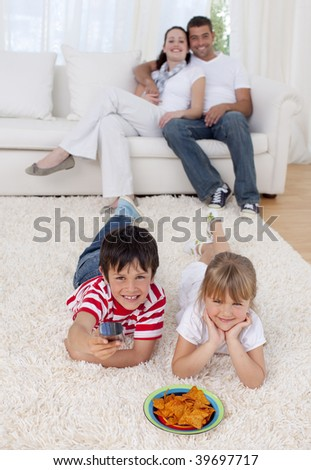 Brother and sister watching television on floor in living-room with their parents on sofa - stock photo
