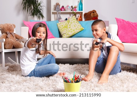 Brother and sister watching TV - stock photo