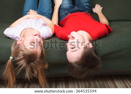 Brother and sister  wearing casual clothes  laying on a green sofa at home stick out tongues teasing each other - stock photo