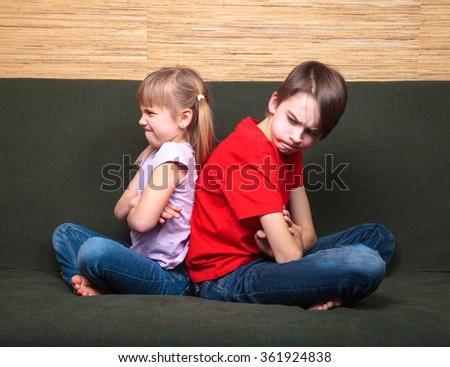 Brother and sister  wearing casual clothes  sitting on a green sofa at home arms crossed back to back angry with each other - stock photo