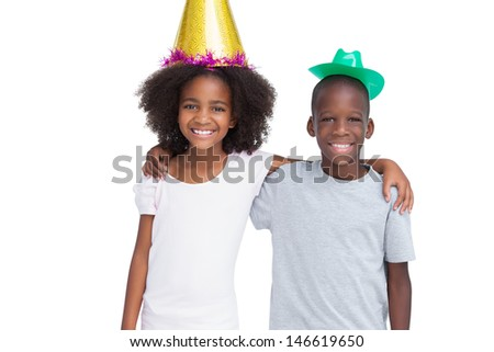 Brother and sister wearing party hats on a white background - stock photo