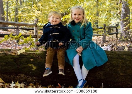 Brother and Sister wearing winter coats sitting together on log in park in autumn