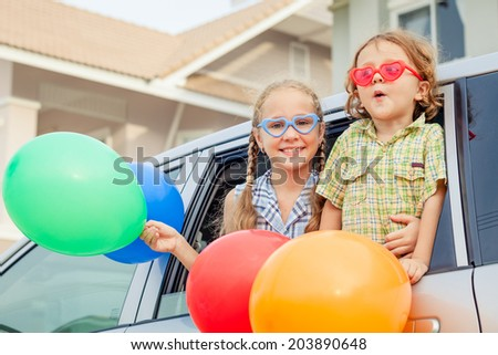 Brother and sister with balloons sitting in the car near window at the day time - stock photo