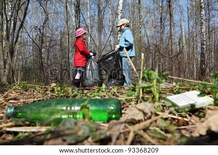Brother and sister with black bags collect trash in park at spring - stock photo