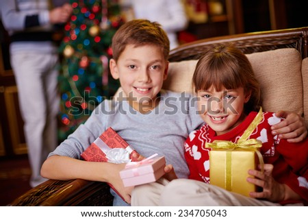 Brother and sister with Christmas gifts looking at camera