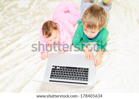 brother and sister with laptop at home, modern communication - stock photo