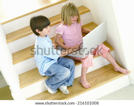Brother and sister (4-8) with laptop on stairs, elevated view (tilt) - stock photo