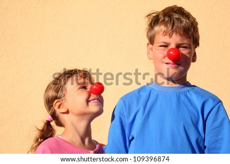 Brother and sister with red clown noses stand near wall and smiles. Girl looks at boy. - stock photo