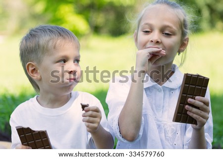 Brother and sister with relish eating chocolate outdoors. - stock photo